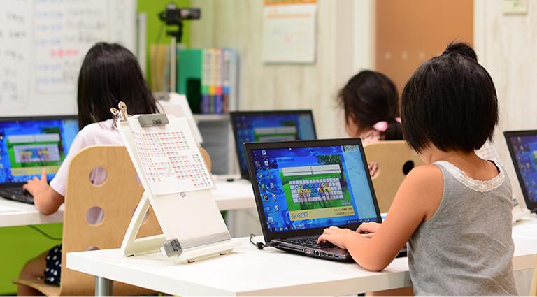 パソコンを操作する子供たちの写真