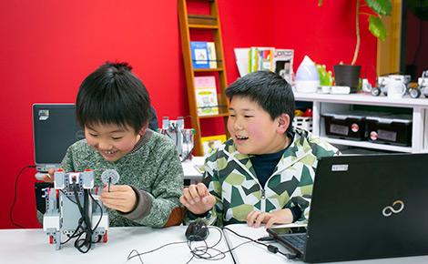 ロボットを動かす子供たちの写真